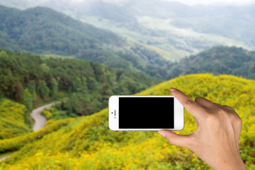 Smart phone in hands of women and mountains in the background