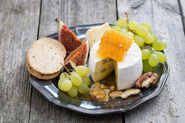 fresh camembert with honey, grapes and crackers on a plate