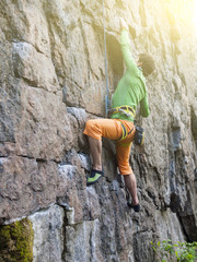 Rock climber climbs the wall.