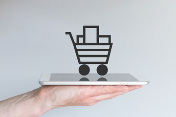 Hand holding smartphone with online shopping cart as symbol