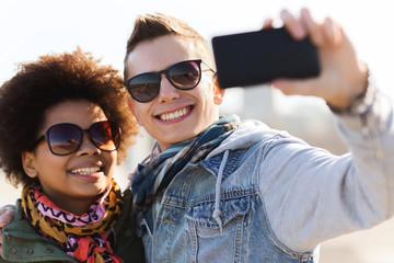 happy teenage friends in shades taking selfie