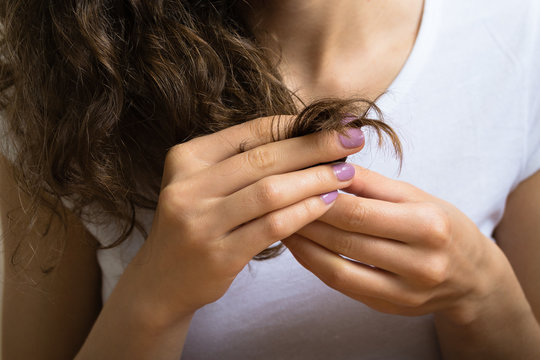 Female hand of a young girl holding the ends of her curly hair