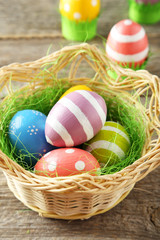 Easter eggs in nest on grey wooden background