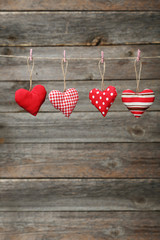 Love hearts hanging on rope on grey wooden background