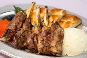 Delilcious lamp chops served in a white plate.