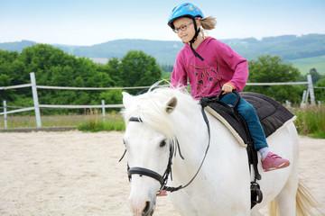 Mädchen reitet auf Pferd