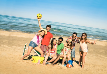Group of multiracial happy friends having fun with beach sport