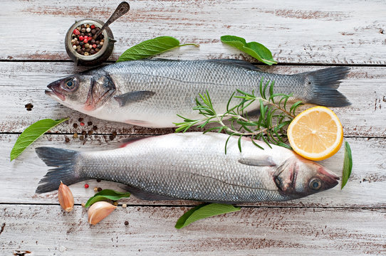 Two raw seabass with spices on an old wooden background