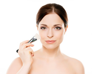 Beauty portrait of young woman holding makeup brushes
