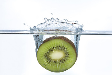 Piece of a kiwi falling into water with a splash