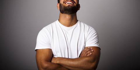 Hombre joven con barba y camiseta blanca con brazos cruzados