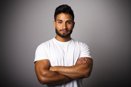 Joven latino con barba y brazos cruzados