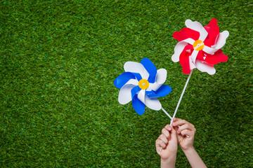 Hands holding pinwheels over grass