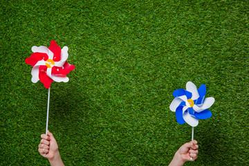 Human hands holding pinwheels over grass