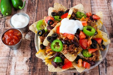 Fully loaded Mexican nachos on rustic wood background