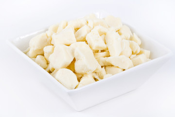 white dairy cheese curd in a bowl over white background