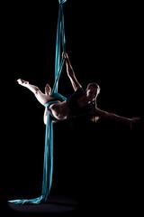 Young woman gymnast with blue gymnastic aerial silks