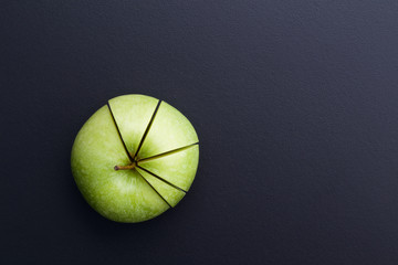 green apple cutting in the shape of pie chart on back board