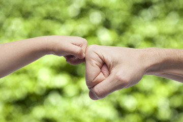 father and son punching fists on green natural background