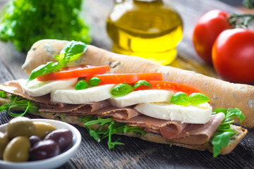 Sandwich with crispy baguette on a wooden background