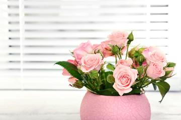 Beautiful roses in pot on windowsill