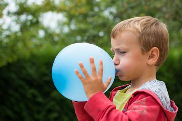 enfant soufflant dans un ballon