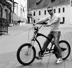 handsome young guy in sunglasses with bicycle