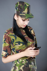 Female American soldier reading a text message