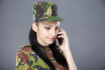 Image of attractive female soldier talking on cell phone against
