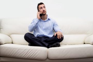 uomo di affari seduto su divano con smartphone che telefona