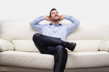 uomo di affari seduto su divano felice e sorridente