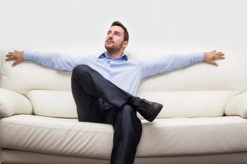 uomo di affari seduto su divano rilassato