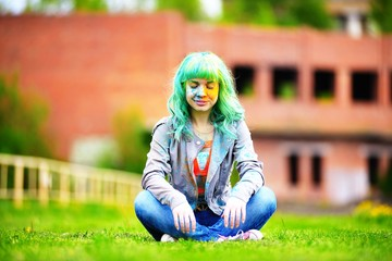 Beautiful alternative young woman with green hair sits on grass
