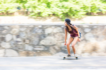 Beautiful mixed race girl skating in the city, panning