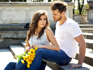 Portrait of unusual couple with yellow tulips sitting and restin