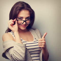 Happy smiling young woman in glasses showing thumb up. Closeup v