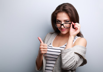 Happy smiling casual woman in glasses showing thumb up