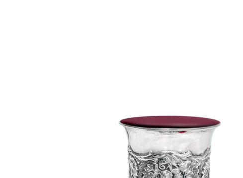 Shabbat silver kiddush cup overflowing with red wine, isolated
