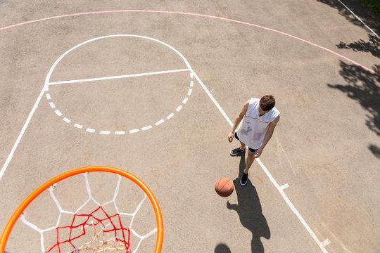 Man Dribbling Basketball in Key of Court