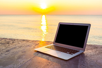 laptop on table at sea sunset in summer time