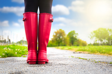 Young woman in pink rain boots walking. detail of boots.