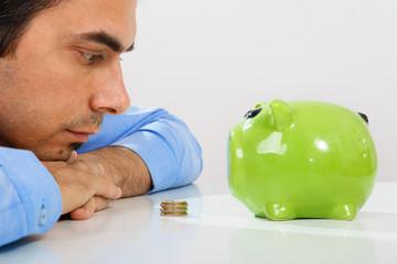 Pensive man looking at green piggy bank