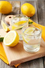 Fresh lemonade with lemon on grey wooden background