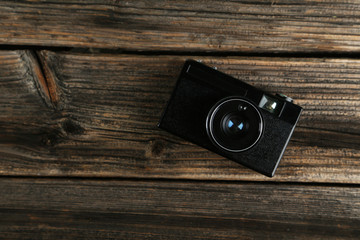 Old retro camera on brown wooden background