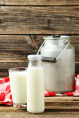Can and glass of milk on brown wooden background