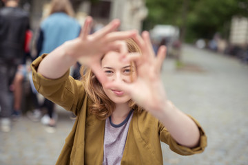 junge frau zeigt ein herz mit ihren händen
