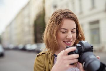 frau in der stadt schaut auf ihre kamera
