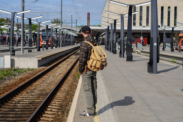 Young man waits train on railway station
