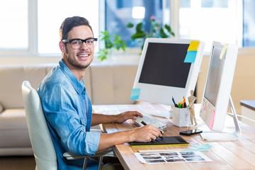 Casual businessman using digitizer at his desk