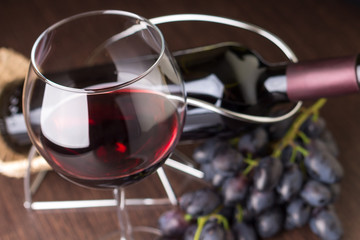 Wineglass with red wine with grapes and bottle at background